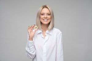 Image of a woman holding a bitcoin in her right hand.
