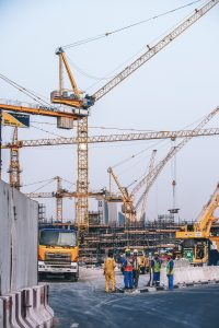 An image of a construction site with numerous high yellow cranes.